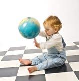 Rapaz pequeno que joga com um globo Imagens de Stock Royalty Free