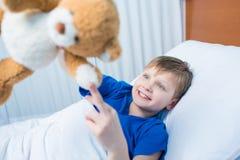 Rapaz pequeno que joga com urso de peluche ao encontrar-se na cama de hospital fotos de stock