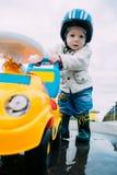 Rapaz pequeno que joga fora com carro Imagens de Stock