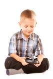 Rapaz pequeno que joga jogos no smartphone Imagens de Stock