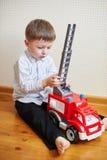 Rapaz pequeno que joga a máquina vermelha do brinquedo na sala Foto de Stock
