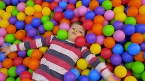 Rapaz pequeno que joga na associação com as bolas plásticas no berçário A criança está nadando Close-up, tempo real, artificial vídeos de arquivo