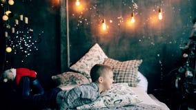 Rapaz pequeno que joga na cama no Natal filme