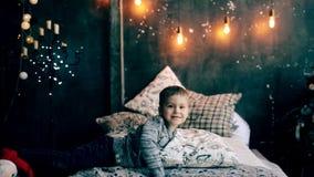 Rapaz pequeno que joga na cama no Natal video estoque