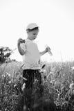 Rapaz pequeno que joga no campo Imagem de Stock