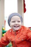 Rapaz pequeno que joga no campo de jogos no parque do outono Imagens de Stock Royalty Free