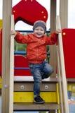 Rapaz pequeno que joga no campo de jogos no parque do outono Fotografia de Stock Royalty Free