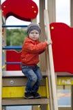 Rapaz pequeno que joga no campo de jogos no parque do outono Fotografia de Stock