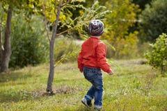 Rapaz pequeno que joga no campo de jogos no parque do outono Imagem de Stock