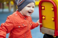 Rapaz pequeno que joga no campo de jogos no parque do outono Imagens de Stock