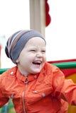Rapaz pequeno que joga no campo de jogos no parque do outono Fotos de Stock