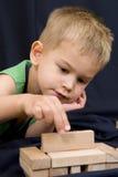 Rapaz pequeno que joga no fundo preto Imagem de Stock Royalty Free