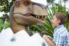 Rapaz pequeno que joga no parque de Dino da aventura fotos de stock