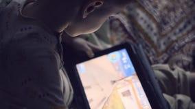 Rapaz pequeno que joga nos jogos de tablet pc video estoque