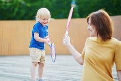 Rapaz pequeno que joga o badminton com a mamã no campo de jogos Imagens de Stock Royalty Free