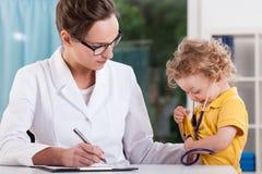 Rapaz pequeno que joga o doutor durante a visita médica Imagens de Stock