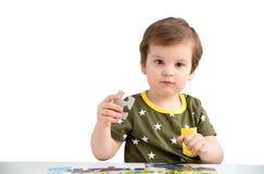 Rapaz pequeno que joga o enigma em um fundo branco Fotos de Stock Royalty Free