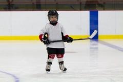 Rapaz pequeno que joga o hóquei em gelo fotografia de stock