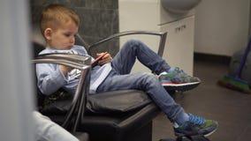 Rapaz pequeno que joga o jogo no assento smartphonewhile em uma cadeira filme