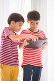 Rapaz pequeno que joga a tabuleta em casa imagens de stock royalty free