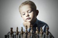 Rapaz pequeno que joga a xadrez Miúdo esperto Criança pequena do gênio Jogo inteligente Tabuleiro de xadrez Fotografia de Stock
