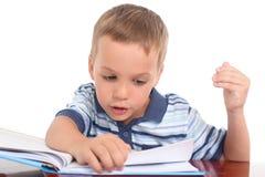 Rapaz pequeno que lê um livro Fotos de Stock