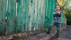 Rapaz pequeno que levanta na câmera perto da cerca de madeira velha, retrato do menino íngreme no tampão video estoque