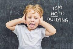 Rapaz pequeno que levanta-se para si mesmo e que diz NÃO a tiranizar fundindo uma framboesa na intimidação na frente de um quadro imagem de stock