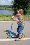 Rapaz pequeno que monta um 'trotinette' Fotos de Stock