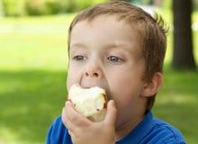 Menino que come uma maçã Fotos de Stock Royalty Free