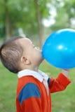 Rapaz pequeno que morde o balão fotos de stock royalty free