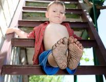Rapaz pequeno que mostra fora seus pés sujos Imagem de Stock Royalty Free