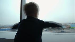 Rapaz pequeno que mostra o plano com as mãos que olham o video estoque