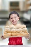 Rapaz pequeno que mostra seu pão Imagem de Stock