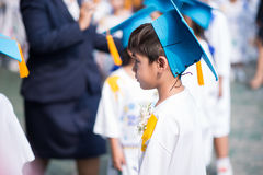 Rapaz pequeno que mostra uniforme graduado do chapéu na escola do jardim de infância Foto de Stock