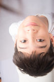 Rapaz pequeno que olha acima com sorriso no fundo branco Imagem de Stock Royalty Free
