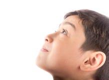 Rapaz pequeno que olha acima com sorriso no fundo branco Imagem de Stock