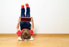 Rapaz pequeno que olha a almofada de toque Imagens de Stock