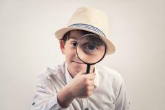 Rapaz pequeno que olha através de uma lupa contra o fundo cinzento Imagem de Stock Royalty Free