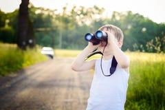 Rapaz pequeno que olha através dos binóculos Imagem de Stock