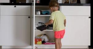 Rapaz pequeno que olha dentro do armário da cozinha