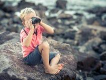 Rapaz pequeno que olha longe com binóculos Imagens de Stock Royalty Free