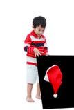 Rapaz pequeno que olha o chapéu de Santa com o quadro-negro, isolado no wh Foto de Stock