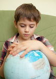 Rapaz pequeno que olha o globo Fotografia de Stock Royalty Free