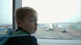 Rapaz pequeno que olha para fora a janela e que aponta em video estoque