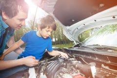 Rapaz pequeno que olha seu pai trabalhar no motor de automóveis Fotos de Stock Royalty Free