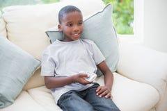 Rapaz pequeno que olha a tevê no sofá Imagens de Stock