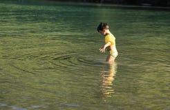 Rapaz pequeno que pensa sobre uma nadada no mar Imagem de Stock