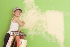 Rapaz pequeno que pinta a parede Imagem de Stock Royalty Free