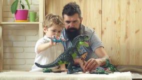 Rapaz pequeno que plaing com paizinho Infância feliz Cuidado e desenvolvimento Pai com construtor da brincadeira Família feliz e filme